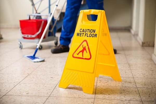janitor mopping floor to avoid slips and falls