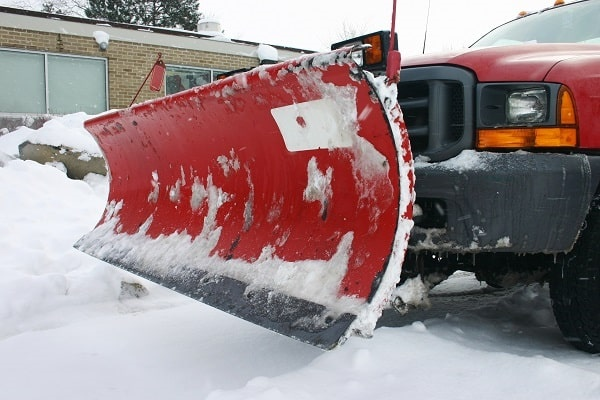 snow plow ensuring winter parking lot is safe